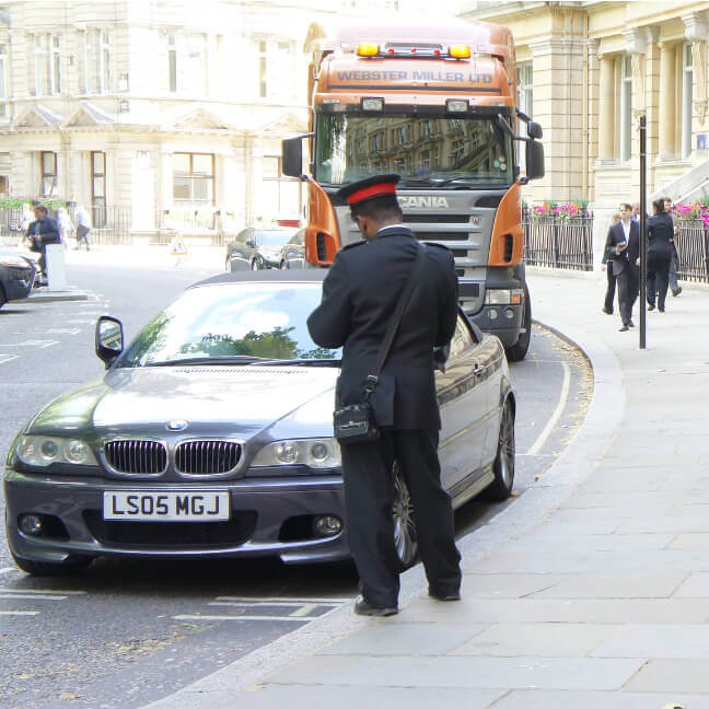 Traffic warden writes a parking ticket for a BMW