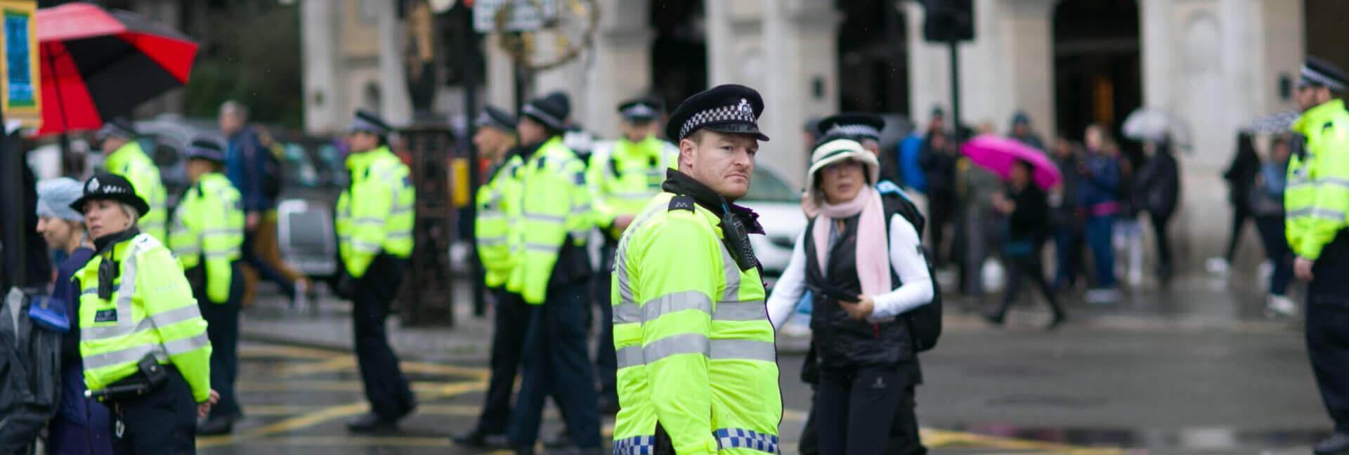 Mehrere Polizisten in gelber Weste bei regnerischem Wetter.