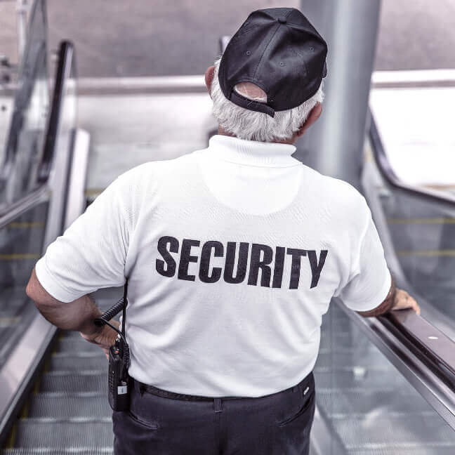 Security Officer with white shirt on escalator