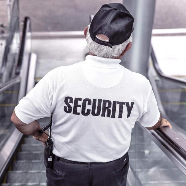 Sicherheitsbeamter mit weißem Hemd auf der Rolltreppe