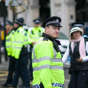 Several police officers in yellow waistcoats in rainy weather.